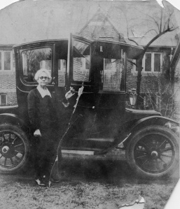 Lizzie George Henderson with her 1912 Detroit Electric car. The original east facade of the library is seen behind her.